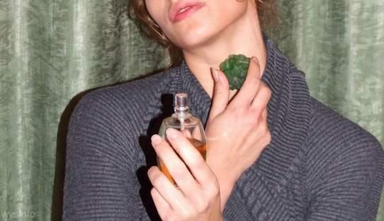 Young woman spraying perfume on neck